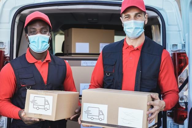 Gemischtrassige arbeiter, die während des ausbruchs des coronavirus kisten mit sicherheitsmasken ausliefern - konzentrieren sie sich auf gesichter
