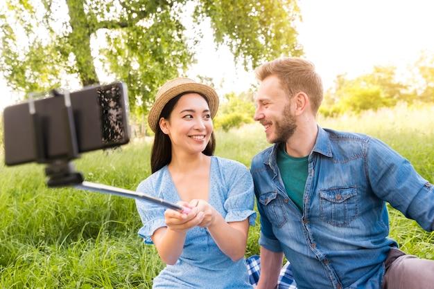 Gemischtrassige erwachsene paare, die selfie mit smartphone nehmen
