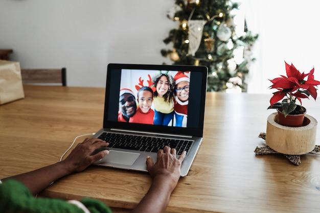 Gemischtrassige familie, die während der weihnachtszeit videoanrufe macht - fokus auf der rechten hand