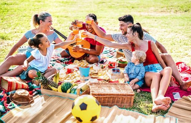 Gemischtrassige familien, die zusammen mit kindern spaß bei einer picknick-grillparty haben