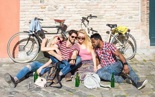 Gemischtrassige freunde, die auf boden im alten stadtzentrum sitzen