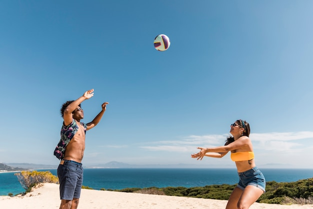 Gemischtrassige freunde, die beachvolleyball spielen