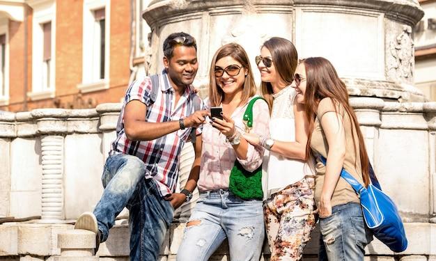 Gemischtrassige freunde, die ein mobiles smartphone bei einer stadtrundfahrt verwenden - glückliches freundschaftskonzept mit studenten, die gemeinsam spaß haben - tausendjährige menschen auf friedensliebeskonzept ohne rassismus - heller außenfilter