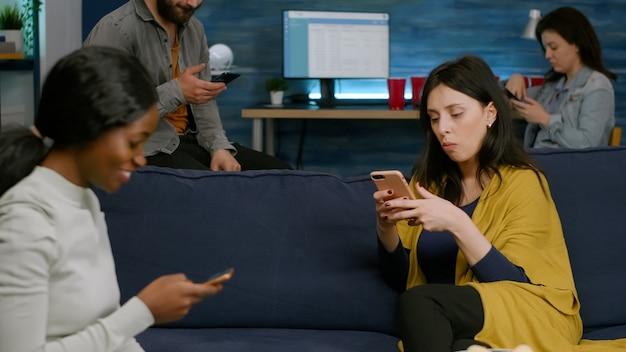 Gemischtrassige freunde, die getrennt auf der couch sitzen, telefonieren und im internet surfen