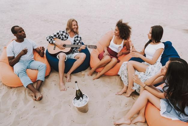 Gemischtrassige freunde, die musik am strandfest spielen