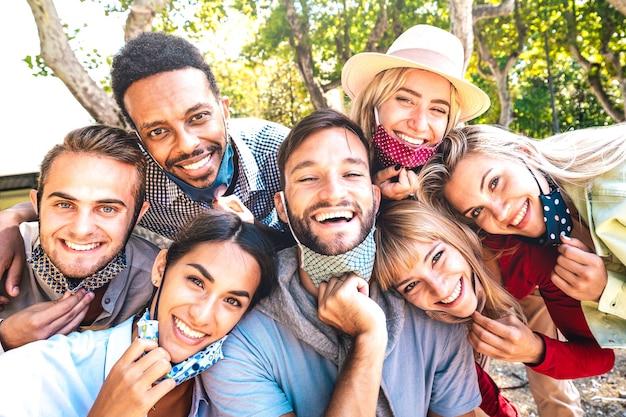 Gemischtrassige freunde, die nach der wiedereröffnung der sperre ein fröhliches selfie mit offenen gesichtsmasken machen