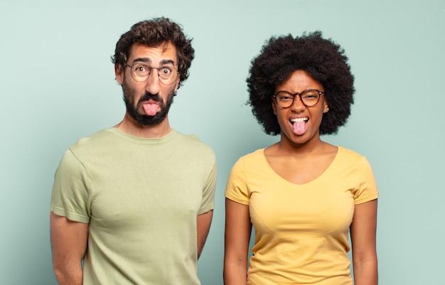 Gemischtrassige freunde, die sich angewidert und gereizt fühlen, die zunge herausstrecken und etwas böses und glückliches nicht mögen