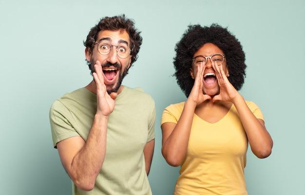 Gemischtrassige freunde, die sich glücklich, aufgeregt und positiv fühlen, mit den händen neben dem mund einen großen schrei ausstoßen und rufen