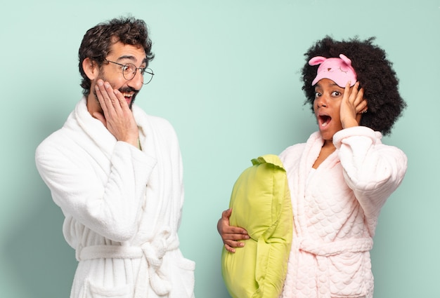 Gemischtrassige freunde, die sich glücklich, aufgeregt und überrascht fühlen und mit beiden händen im gesicht zur seite schauen. pyjama und heimkonzept