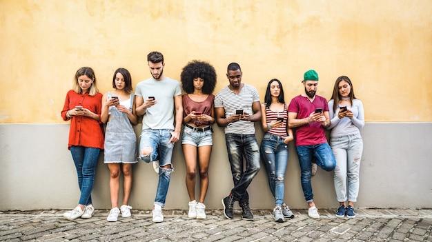 Gemischtrassige freunde, die smartphone gegen wand verwenden