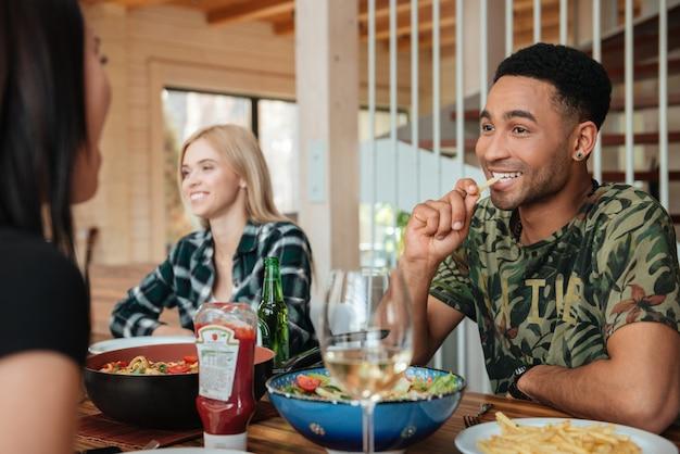 Gemischtrassige freunde, die zu hause am tisch essen, trinken und reden