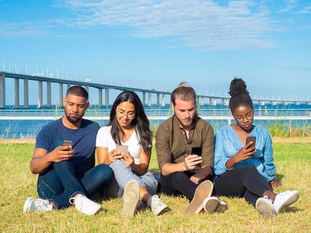 Gemischtrassige freunde, welche die smartphones im freien verwenden