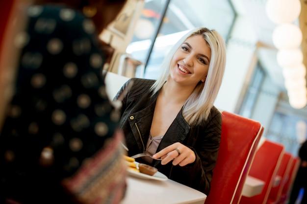 Gemischtrassige freundinnen, die schnellimbiß an einem tisch im restaurant essen