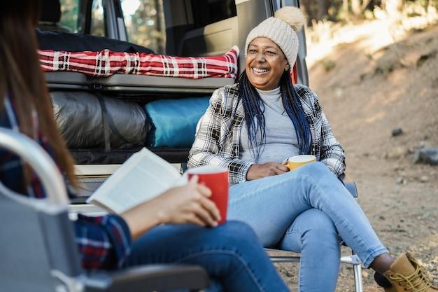 Gemischtrassige freundinnen, die spaß beim campen mit wohnmobil im freien im wald haben - konzentrieren sie sich auf das gesicht der älteren afrikanischen frau