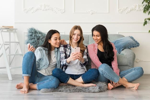 Gemischtrassige freundinnen fotografiert am telefon