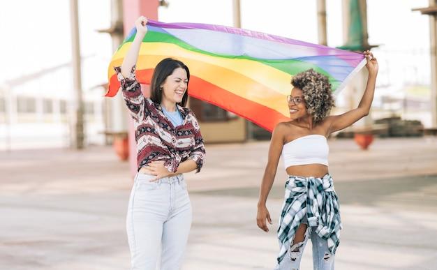 Gemischtrassige freundinnen mit regenbogenflagge, gay pride