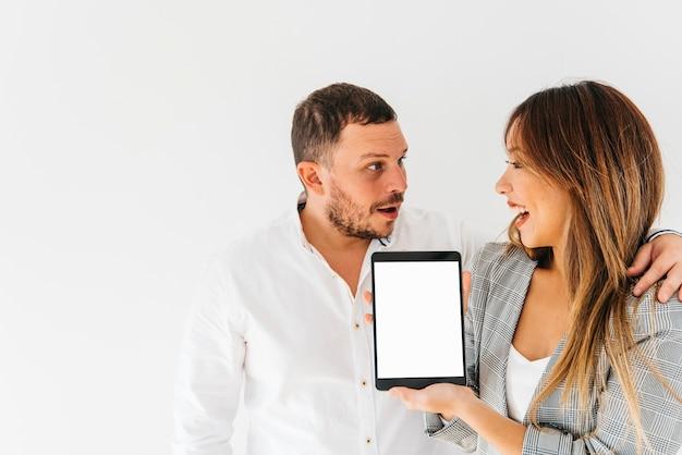 Gemischtrassige freundliche kollegen, die neue tablette vorstellen