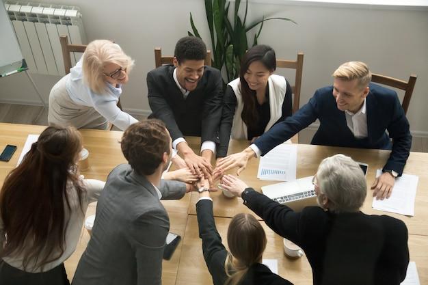 Gemischtrassige geschäftsleute setzen hände bei gruppenteamtreffen zusammen