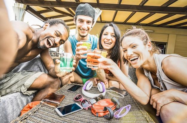Gemischtrassige glückliche freundgruppe, die selfie nimmt und trinkende cocktails des spaßes am strand hat