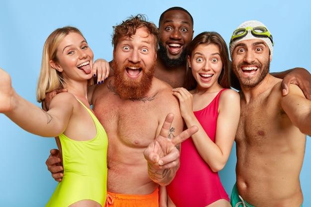 Gemischtrassige gruppe junger freunde, die am strand aufwerfen