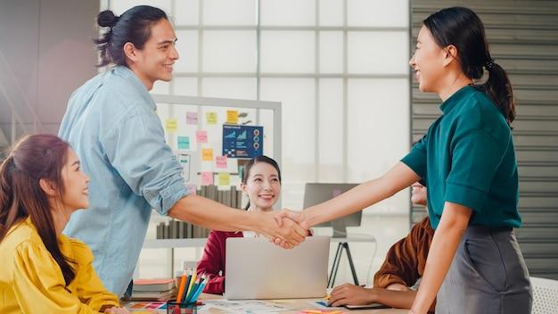 Gemischtrassige gruppe junger kreativer leute in der intelligenten freizeitkleidung, die geschäft, das händeschütteln zusammen und das lächeln während des stehens im modernen büro bespricht. partnerkooperation, mitarbeiter-teamwork-konzept.