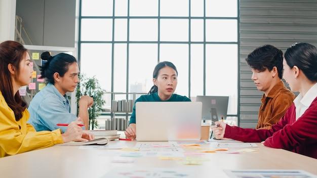 Gemischtrassige gruppe junger kreativer leute in der intelligenten freizeitkleidung, die geschäftsentwirkungs-besprechungsideen-entwurfsprojekt der mobilen anwendungssoftware im modernen büro bespricht. teamwork-konzept für mitarbeiter.