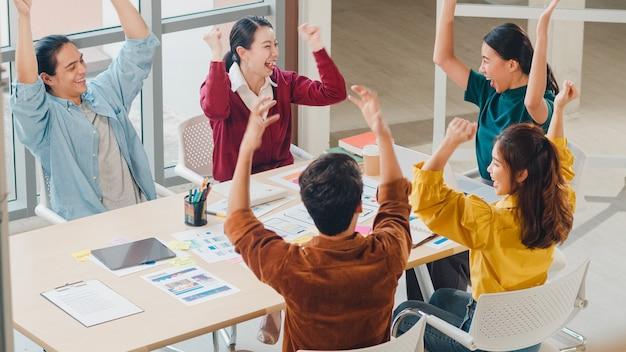 Gemischtrassige gruppe junger kreativer leute in der intelligenten freizeitkleidung, die geschäftsgestenhand hoch fünf bespricht, zusammen lachend und lächelnd im brainstorming-treffen im büro. teamwork-konzept für mitarbeiter.