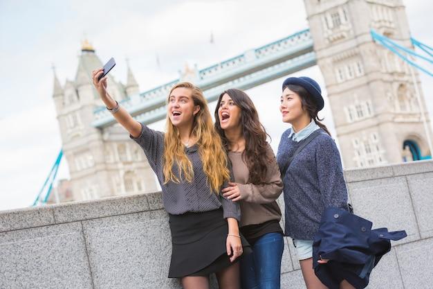 Gemischtrassige gruppe mädchen, die ein selfie in london nehmen