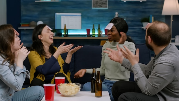 Gemischtrassige gruppe spielt rate mal, wer mit klebrigen papieren an der stirn spielt. multiethnische freunde, die spaß haben, zusammen lachen, während sie spät in der nacht auf dem sofa im wohnzimmer sitzen