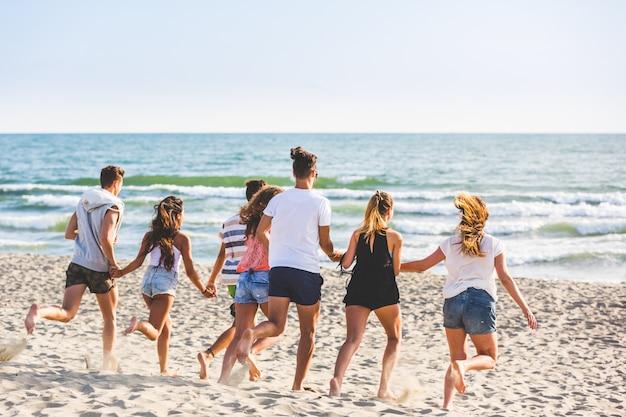 Gemischtrassige gruppe von freunden am strand laufen