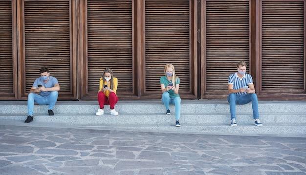 Gemischtrassige gruppe von freunden, die eine schützende gesichtsmaske tragen, während sie das mobiltelefon im freien verwenden - soziales distanzkonzept
