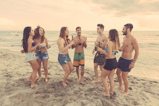 Gemischtrassige gruppe von freunden mit einer party am strand