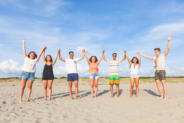 Gemischtrassige gruppe von freunden mit erhobenen händen am strand