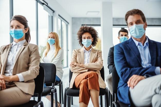 Gemischtrassige gruppe von geschäftsleuten mit gesichtsmasken, die auf dem seminar während des koronavirus sitzen