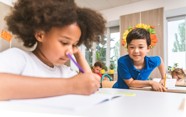 Gemischtrassige gruppe von kindern in der grundschule - spielerische schüler, die die schulzeit und den unterricht mit lehrer und klassenkameraden genießen