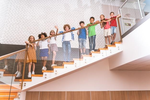 Gemischtrassige gruppe von kindern in der grundschule - verspielte schüler, die die schulzeit und den unterricht mit lehrer und klassenkameraden genießen