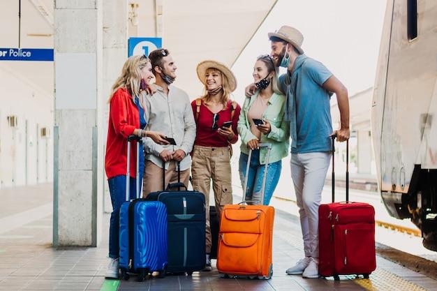 Gemischtrassige gruppe von menschen, die spaß am bahnhof haben. junge freunde, die gesichtsmaske an feiertagen tragen