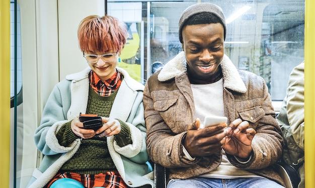 Gemischtrassige hippie-freundpaare, die spaß mit smartphone im u-bahnzug haben