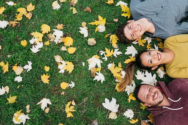 Gemischtrassige junge freunde, die auf gras mit herbstlaub liegen