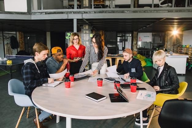 Gemischtrassige junge kreative leute im modernen büro. gruppe junge geschäftsleute arbeiten zusammen mit laptop, tablette, intelligentem telefon, notizbuch. erfolgreiches hipster-team beim coworking. freiberufler.