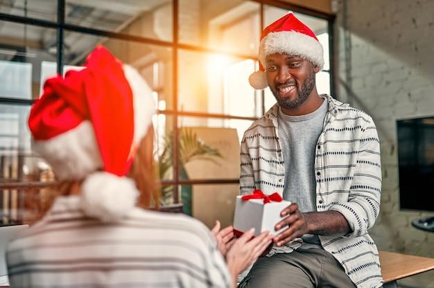 Gemischtrassige junge kreative menschen, die weihnachtsmützen tragen, tauschen am letzten arbeitstag geschenke mit kollegen aus.