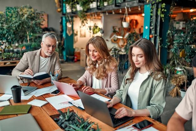 Gemischtrassige kreative leute im modernen büro. gruppe junger geschäftsleute und seniorchef arbeiten mit laptop, tablet, smartphone, notebook, grafiken zusammen. erfolgreiches team im coworking