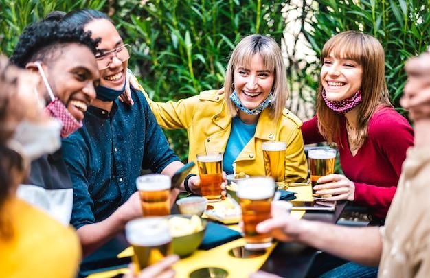 Gemischtrassige menschen, die bier mit geöffneter gesichtsmaske trinken