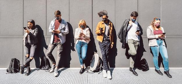 Gemischtrassige menschen, die mobiles smartphone mit abgedeckter gesichtsmaske verwenden