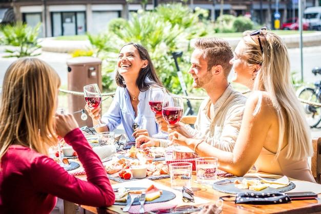 Gemischtrassige menschen trinken rotwein im restaurant mit offener bar