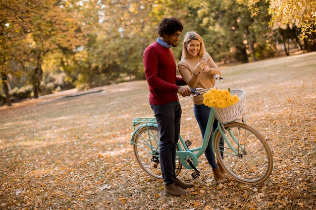 Gemischtrassige paare mit dem fahrrad, das im herbstpark steht und handy verwendet