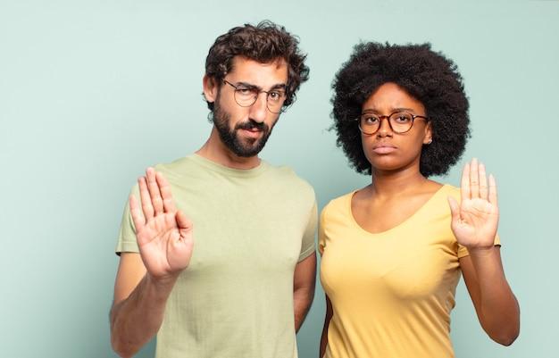Gemischtrassige paare von freunden, die ernst, streng, unzufrieden und wütend aussehen und eine offene handfläche zeigen, die eine stoppgeste macht