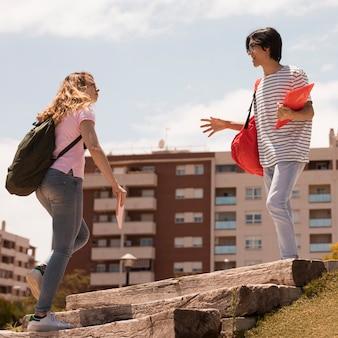 Gemischtrassige studenten auf straßentreppen im sonnenlicht