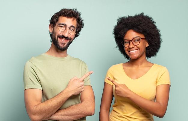 Gemischtrassiges freundespaar, das fröhlich lächelt, sich glücklich fühlt und zur seite und nach oben zeigt und das objekt im kopierraum zeigt