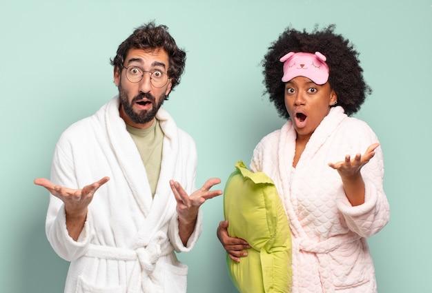 Gemischtrassiges freundespaar, das sich extrem schockiert und überrascht, ängstlich und panisch fühlt, mit einem gestressten und entsetzten blick. pyjamas und wohnkonzept